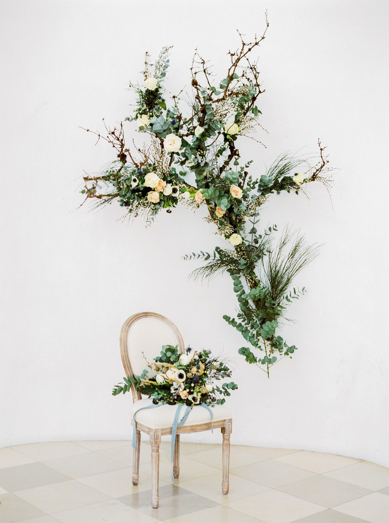 Wedding floral display on wall with bouquet on chair