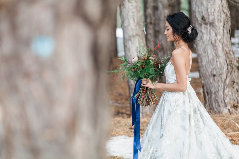 Bride carrying bouquet with blue ribbon