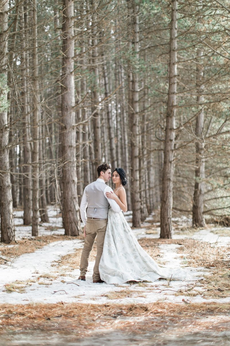 Bride and groom by trees in snow