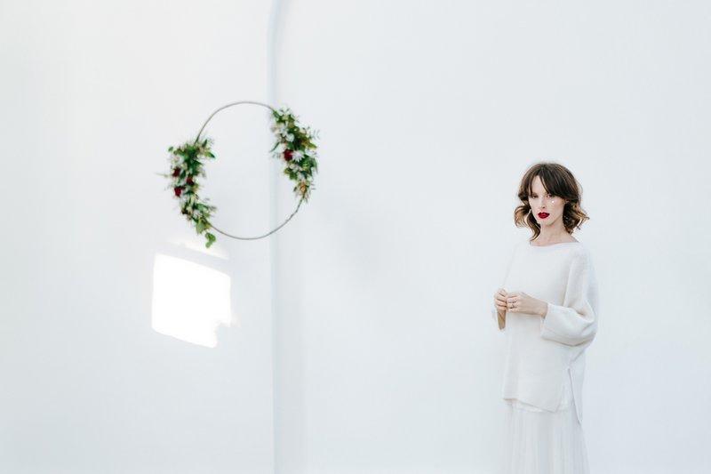 Bride standing by foliage hoop
