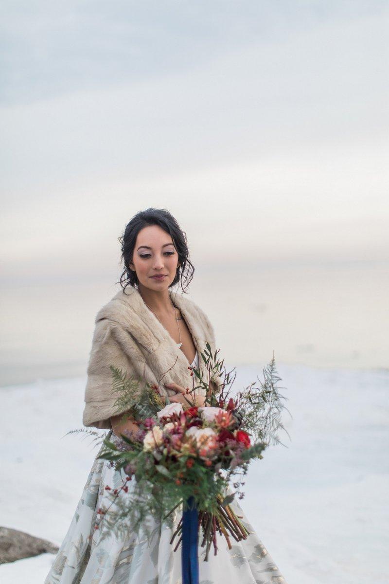 Bride wearing fur shrug holding bouquet