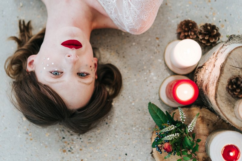 Bride lying down next to candles, logs and winter foliage