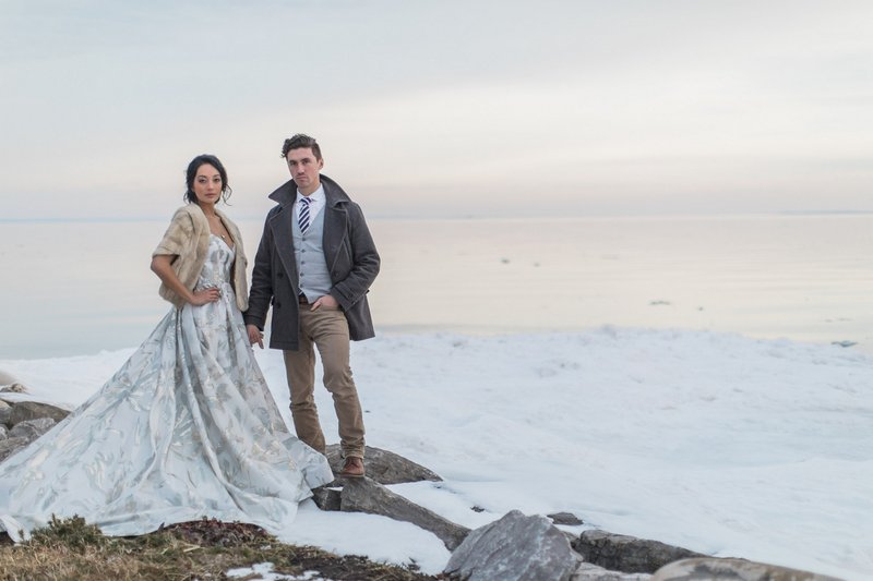 Bride and groom standing on rocks in the snow