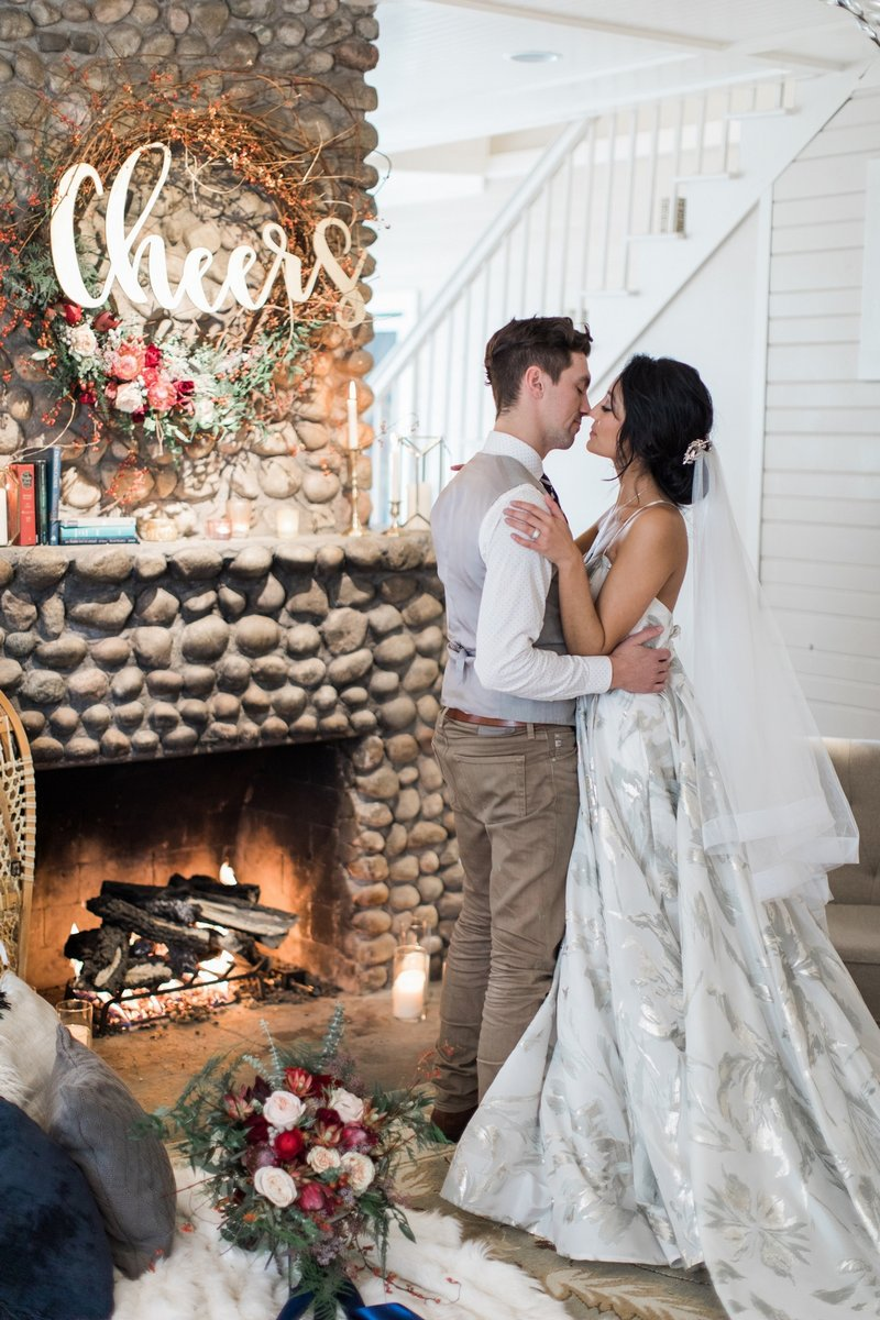 Bride and groom by cosy fireplace