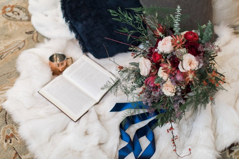 Winter wedding bouquet and book on fur blanket