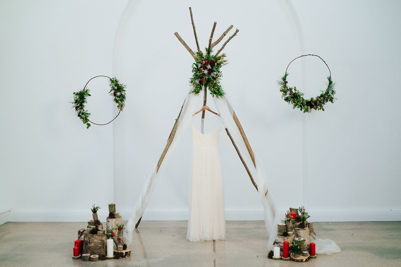 Wedding dress hanging from simple wedding ceremony tipi