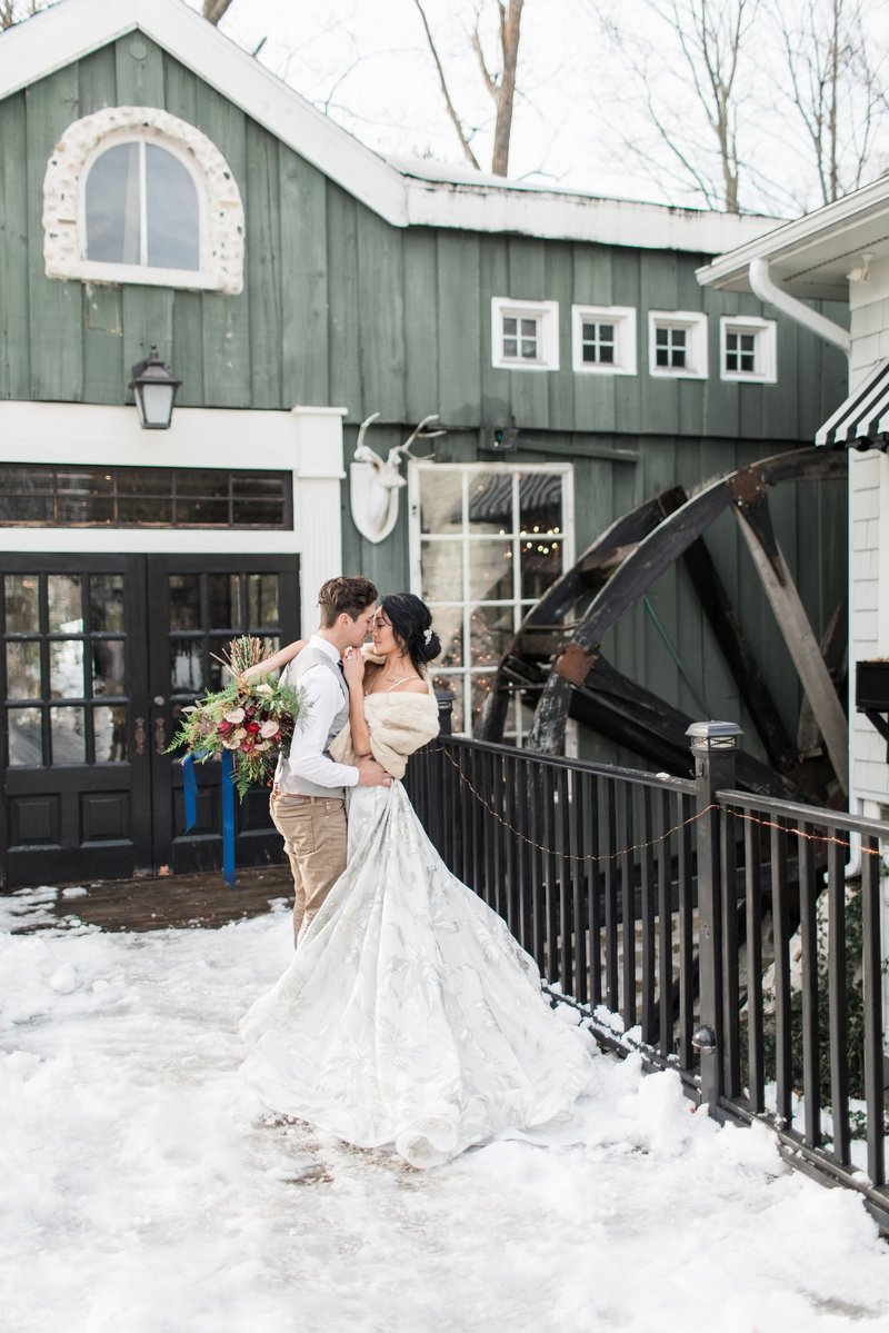 Bride and groom outside Willowbrook Mill in the snow