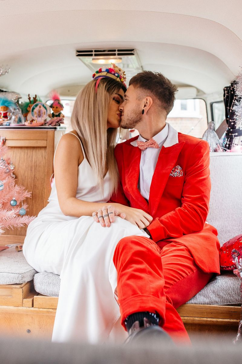 Bride kissing groom in red suit