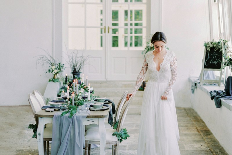 Bride standing next to table with grey wedding styling