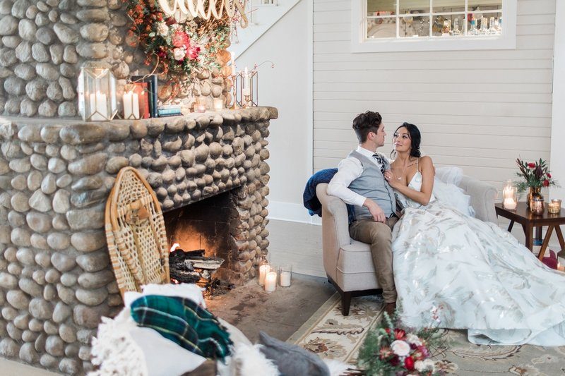 Bride and groom sitting next to fireplace
