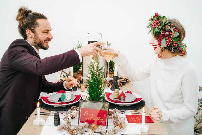 Bride and groom sitting at wedding table with red, green and black winter styling