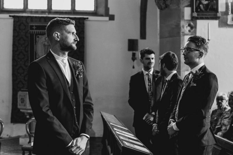 Nervous groom waiting for bride at altar