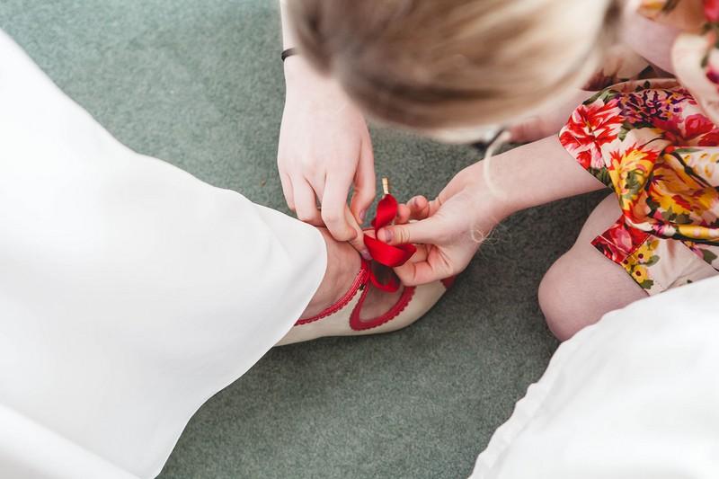 Bridesmaid doing up ribbon bride's shoe