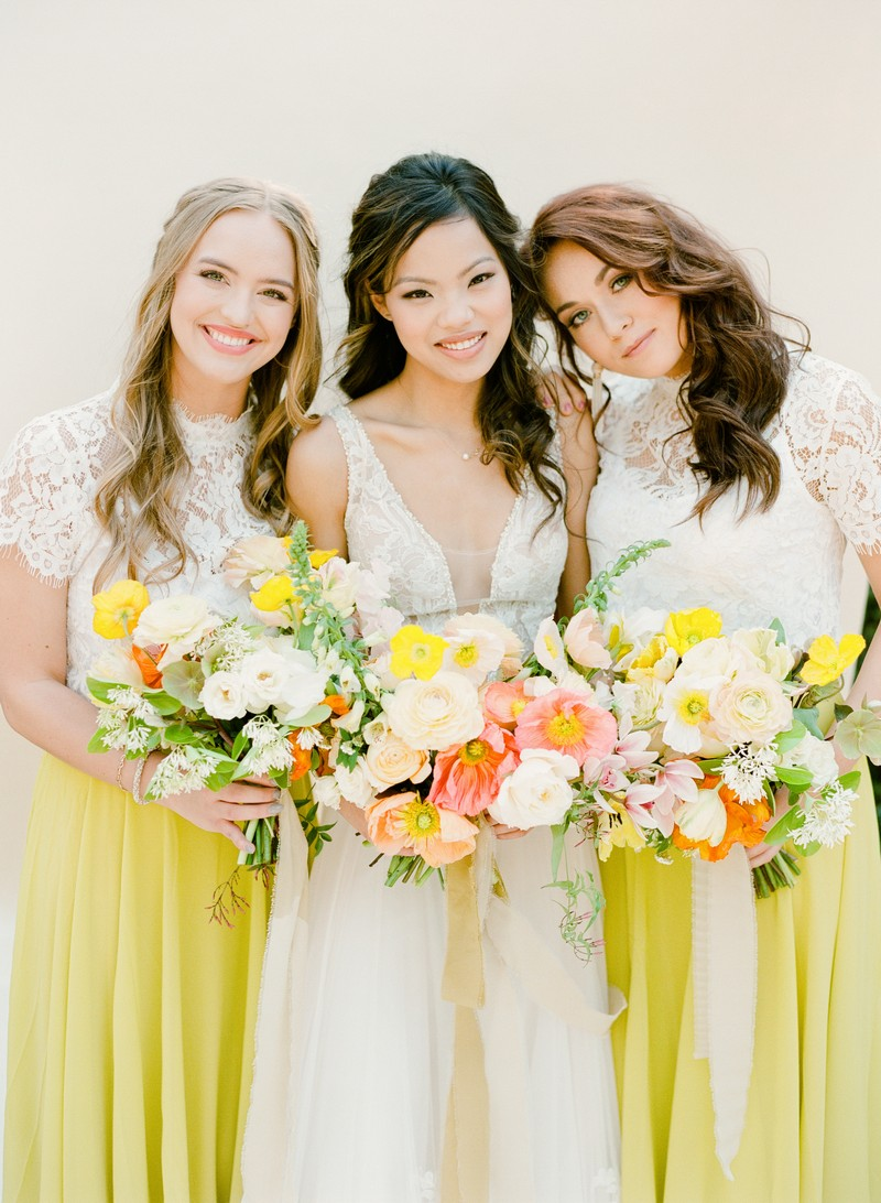 Bride with bridesmaids in yellow skirts holding colourful bouquets