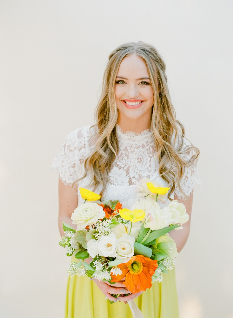 Bridesmaid with white lace top holding yellow, white and green bouquet