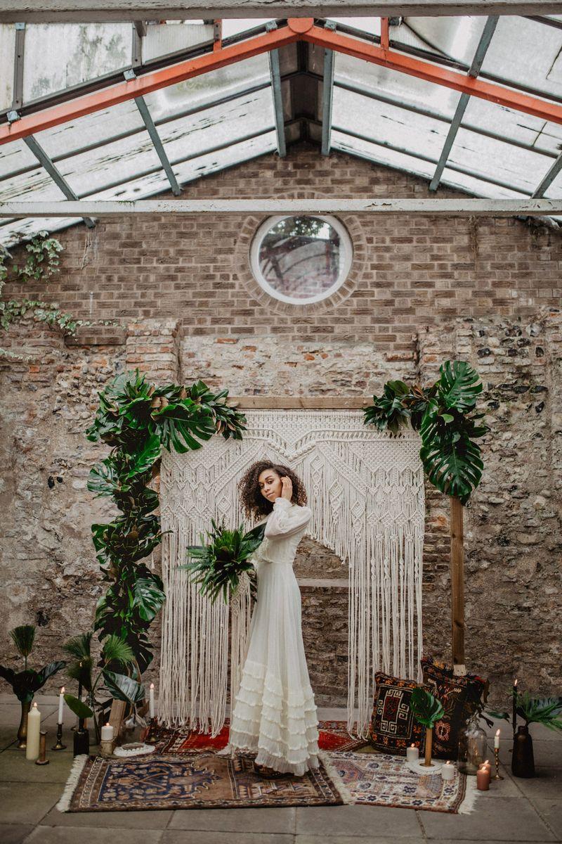 Bride standing in front of macramé wedding backdrop