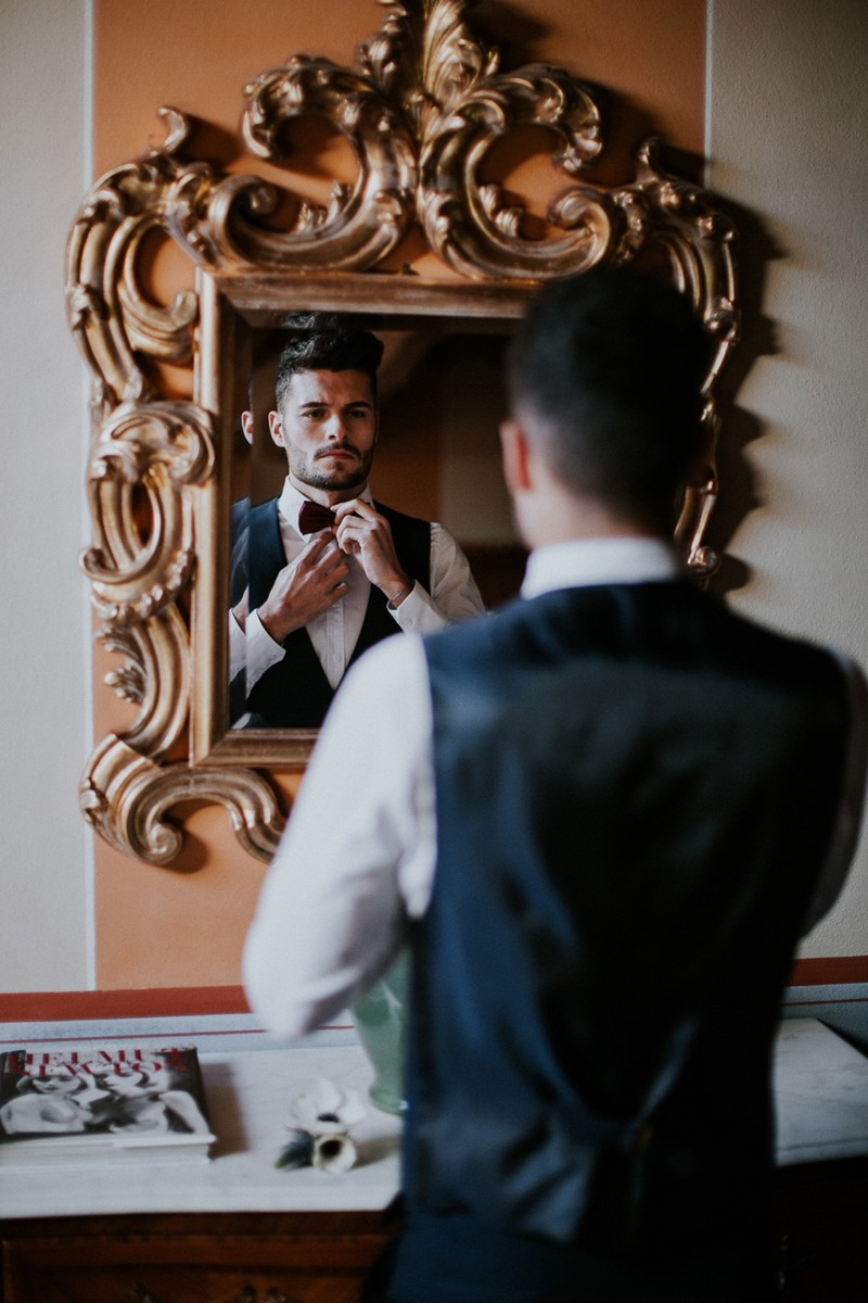 Groom doing bow tie in mirror