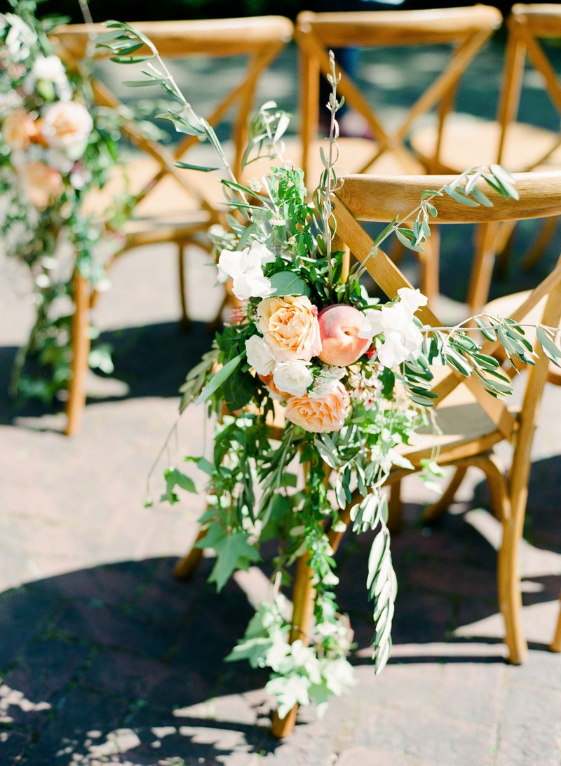 Foliage and peach flowers tied to wedding chair