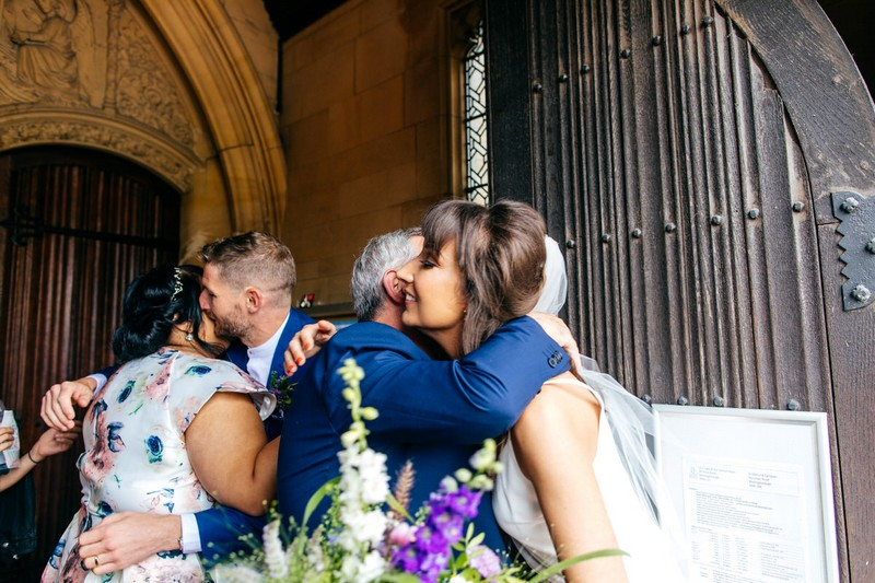 Bride and groom hugging wedding guests outside church