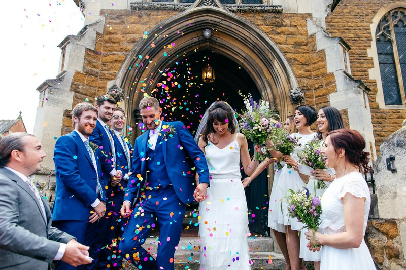 Bride and groom being showered in confetti as they walk down steps of church