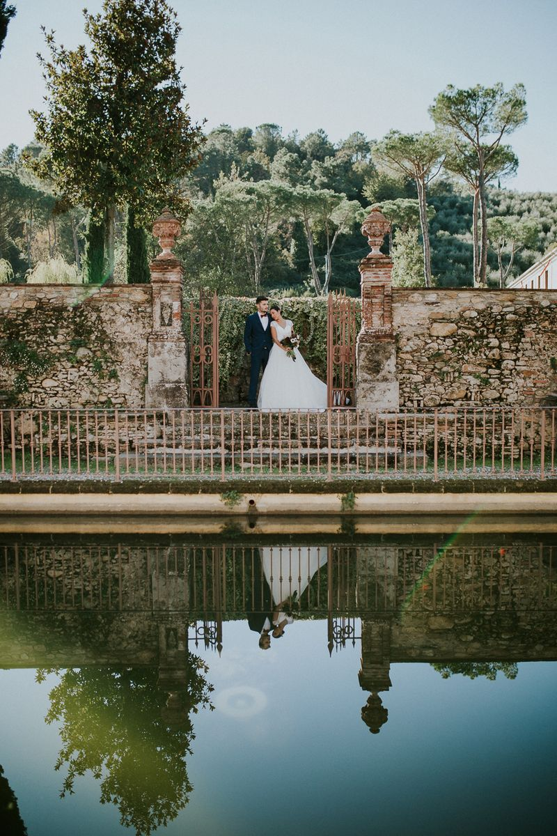 Bride and groom by water in Tuscany