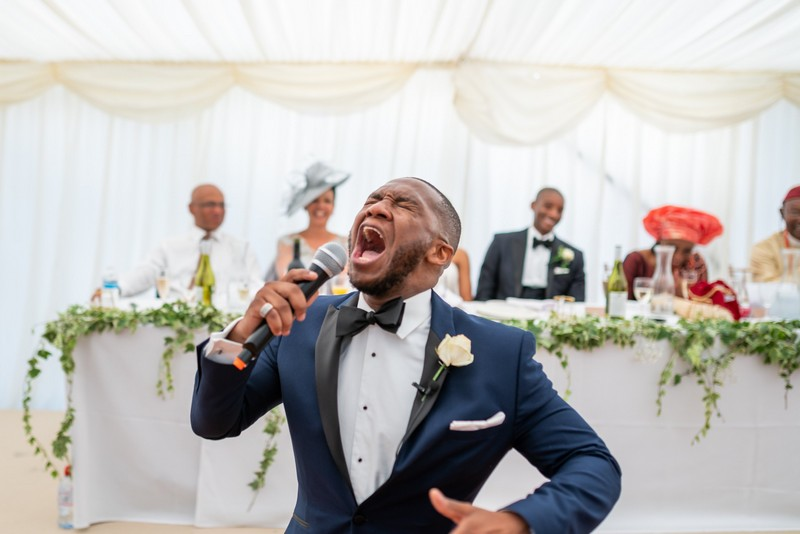 Man singing passionately in front of top table at wedding - Picture by Moritz Schmittat Photography