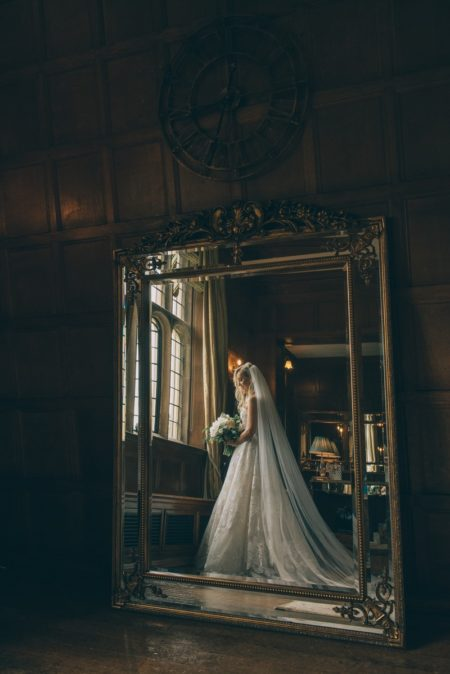 Reflection in mirror of bride standing by window - Picture by Emma-Jane Photography