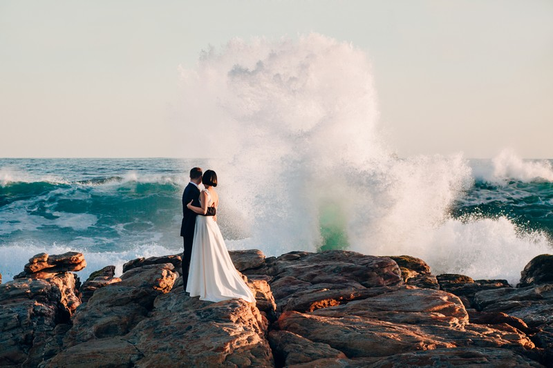 Bride and groom standing on rocks as big wave crashes in front of them - Picture by Estefania Romero Photography