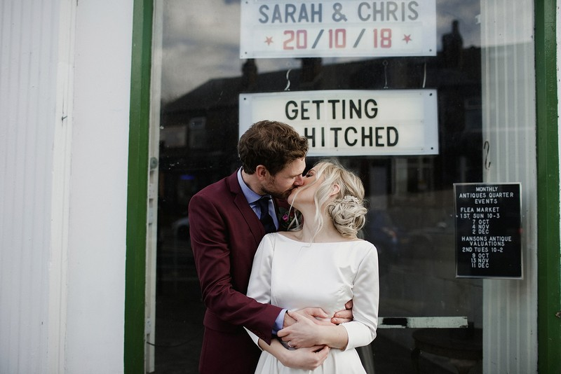 Bride and groom kissing in front of window with Getting Hitched sign - Picture by Jess Petrie Photography