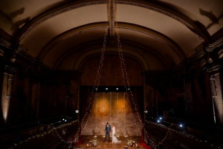 Bride and groom on stage Wiltons Music Hall wedding venue - Picture by Voyteck Photography