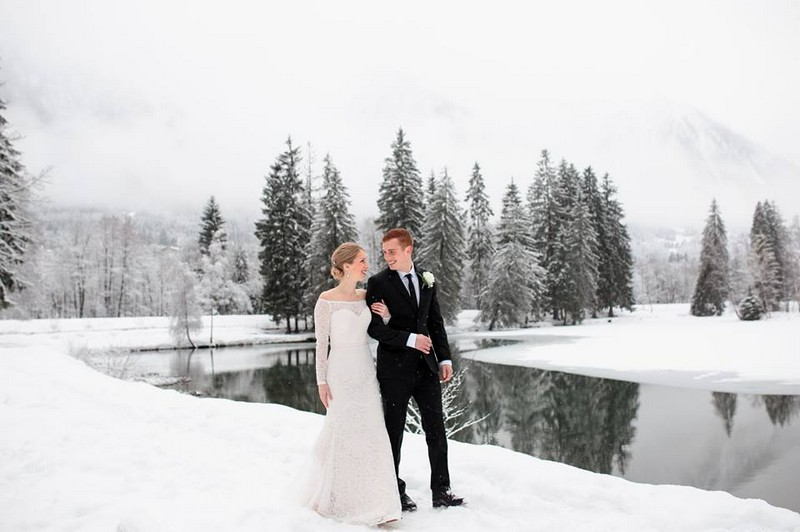 Bride and groom walking by lake in the snow - Picture by Airsnap