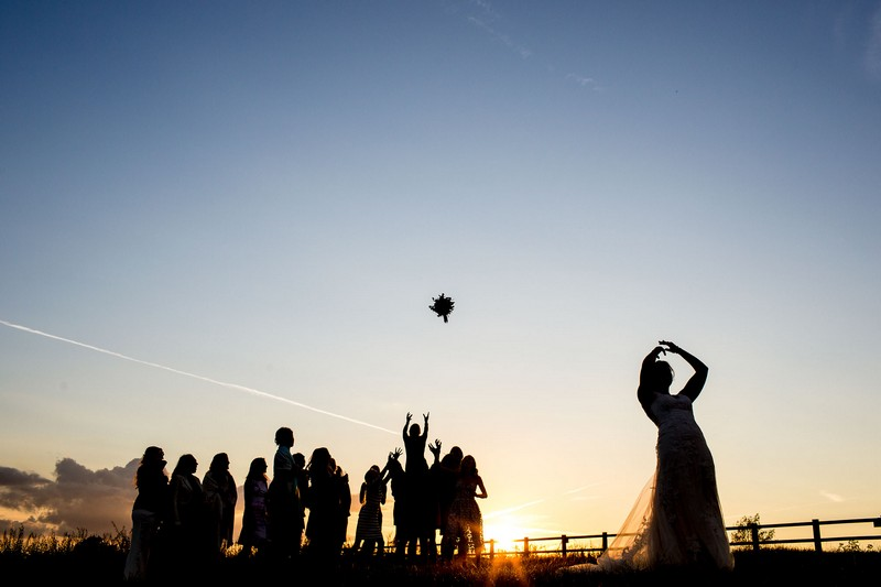 Silhouette of bride throwing bouquet to guests at sunset - Picture by Aaron Storry Photography