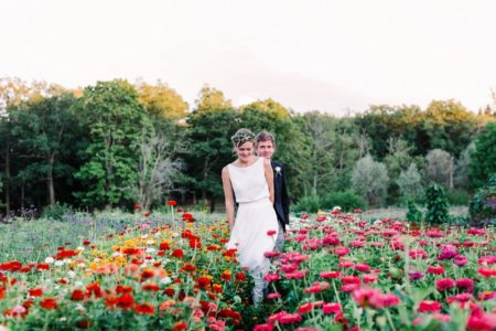 Bride and groom walking through colourful flowers - Picture by Anette Bruzan Photography