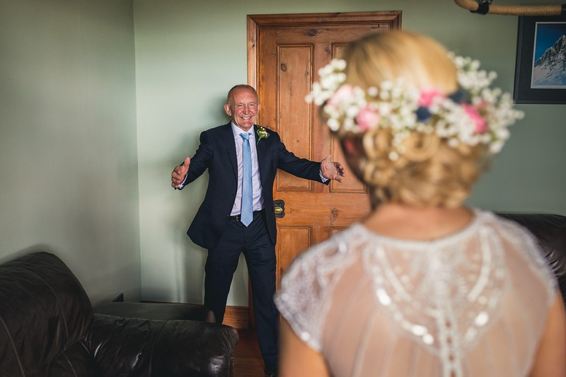 Happy father with arms out ready to hug bride - Picture by Andy Hudson Photography
