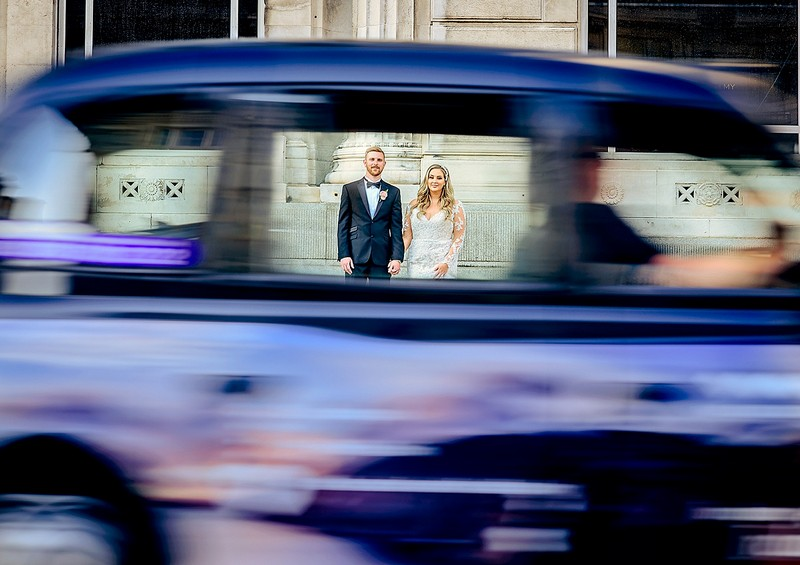 Bride and groom seen through window of blurred car driving past - Picture by Mick Cookson Photography