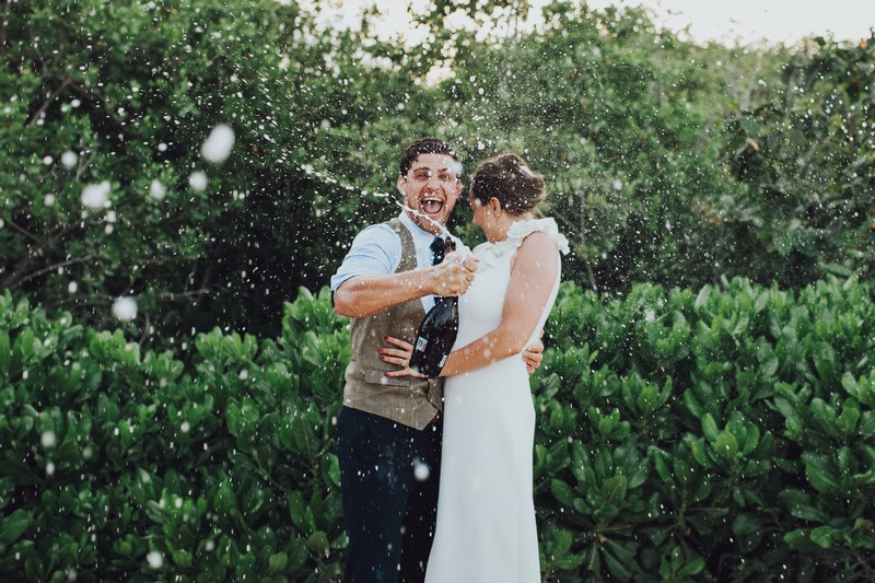 Groom spraying Champagne everywhere as bride turns away - Picture by Honeydew Moments