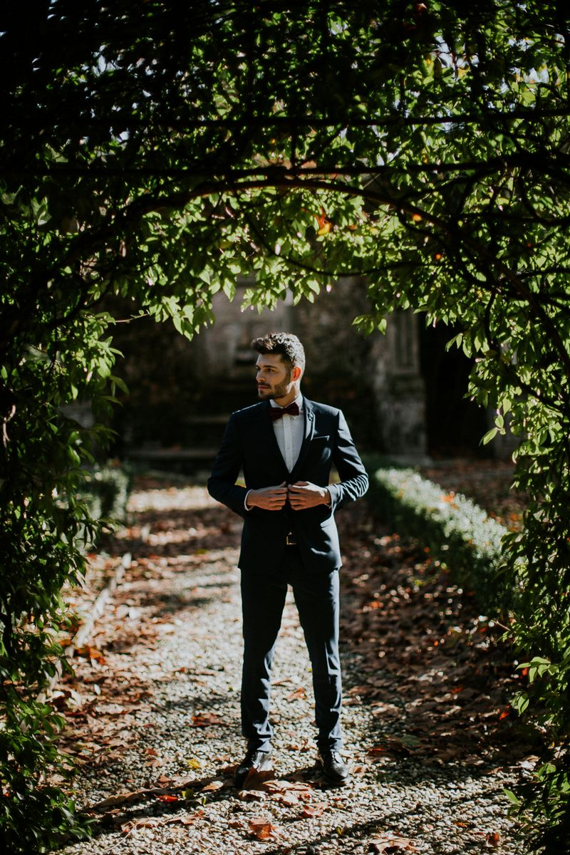 Groom standing under tree in Tuscany