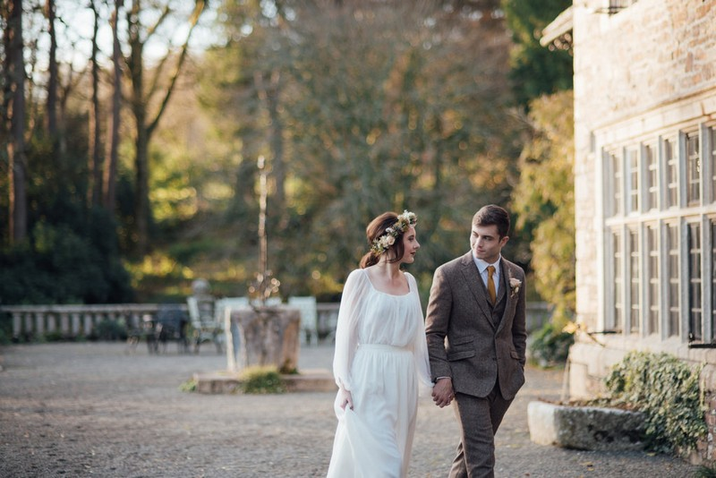 Bride and groom walking in grounds of Coombe Trenchard