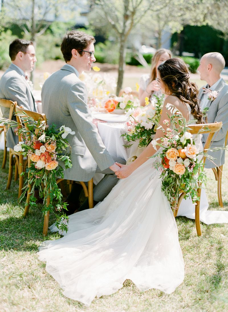 Bride and groom sitting on wedding chairs with flowers
