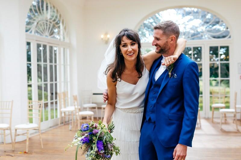 Bride with arm around groom's shoulders