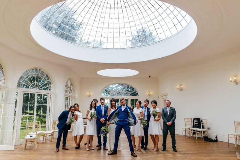 Groom standing in front of bridal party holding jacket out