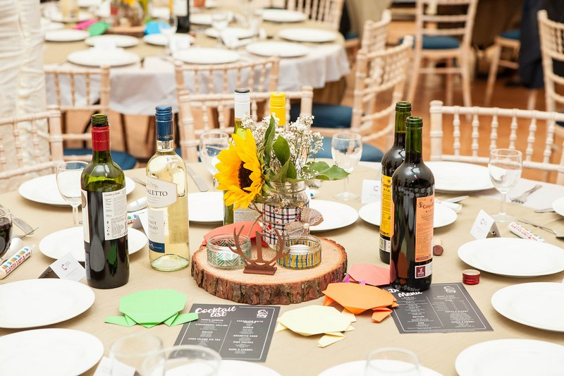 Sunflower in jar on top of log slice on wedding table