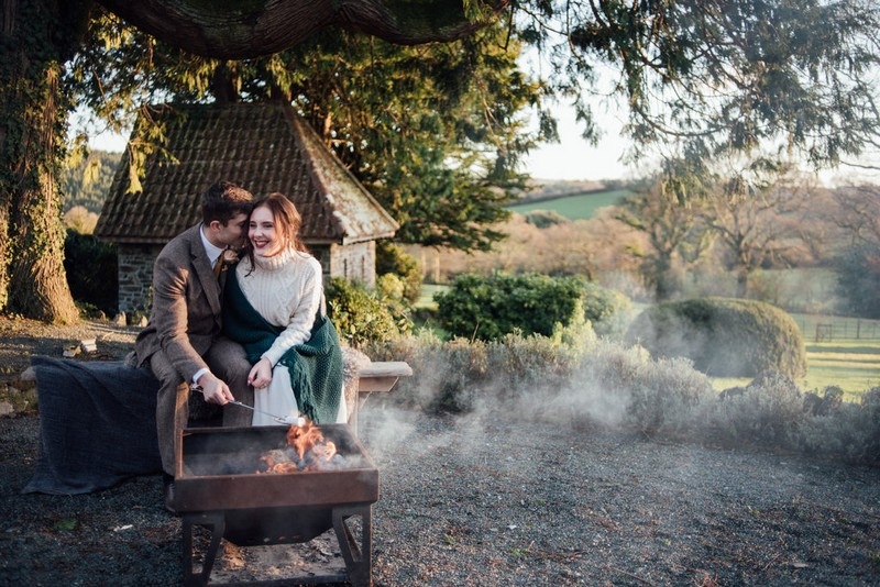 Bride and groom toasting marshmallows over fire