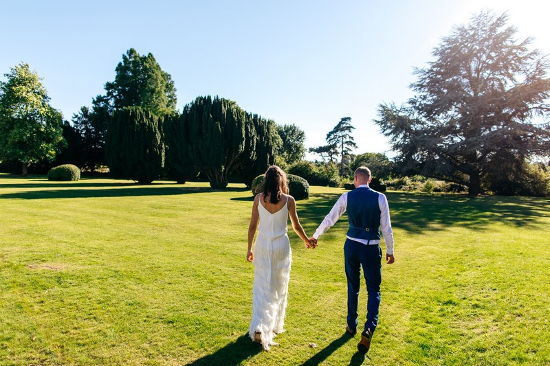 Bride and groom walking in grounds of Barton Hall
