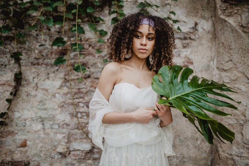 Bride holding large tropical palm leaf