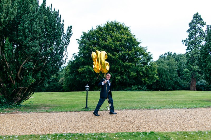 Man carrying balloons to wedding ceremony