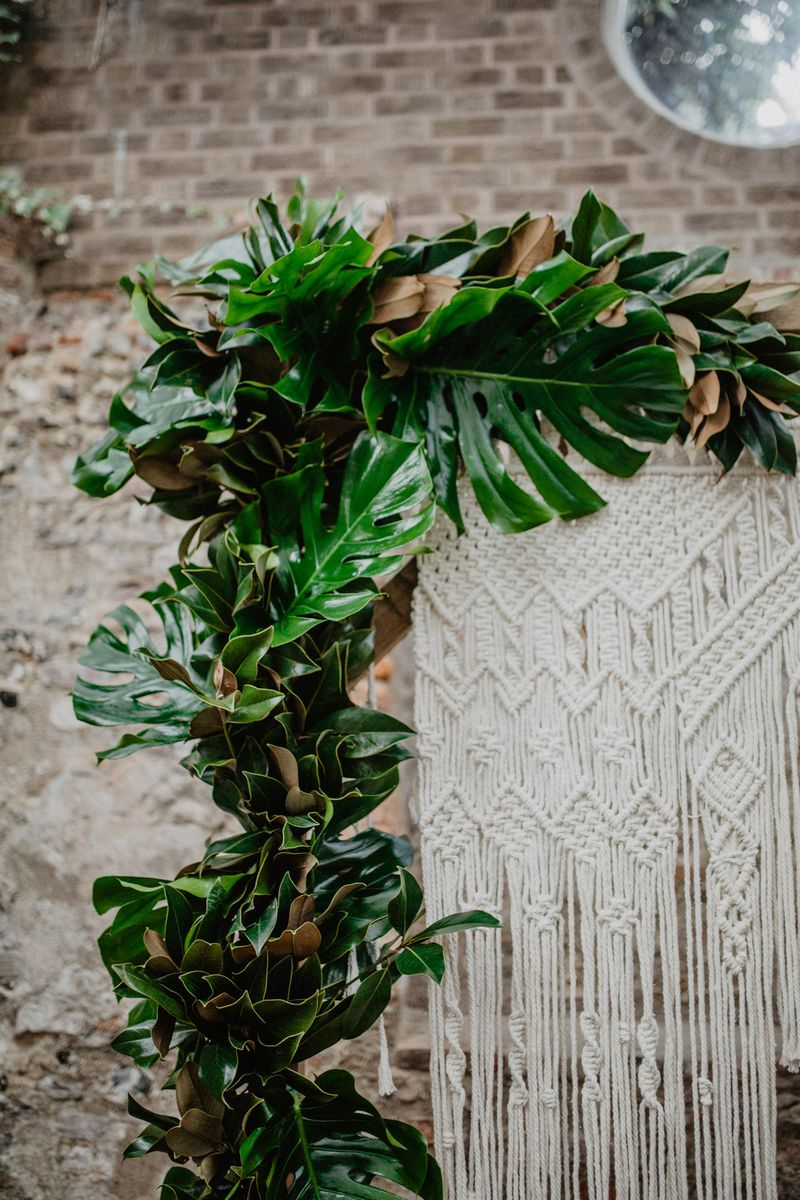 Tropical palm leaves around macramé wedding backdrop