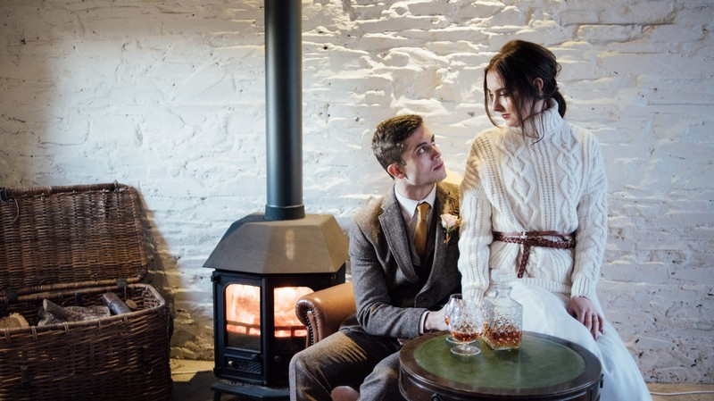 Bride and groom sitting by log burner in Coombe Trenchard