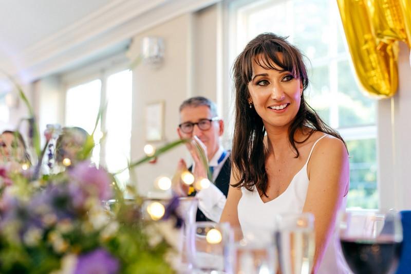 Bride looking at groom as he gives wedding speech