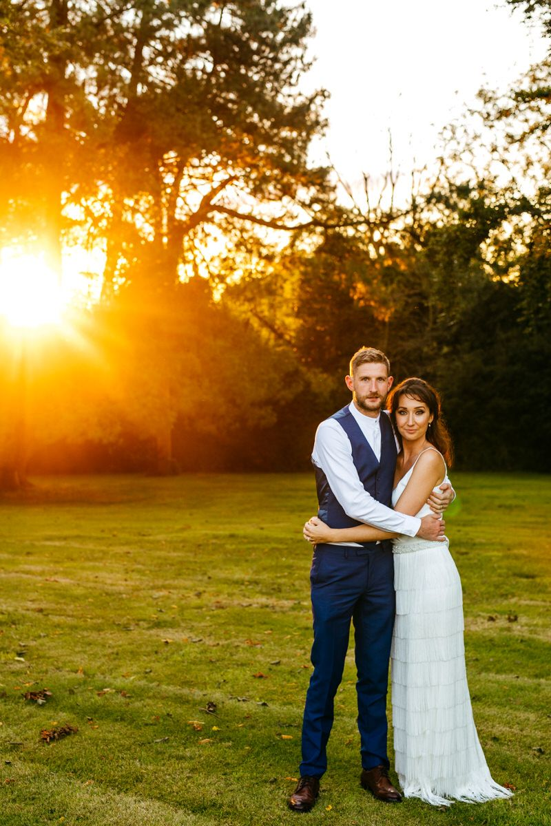 Bride and groom in grounds of Barton Hall with sun shining through trees
